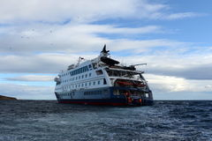 Tourists disembark from cruise ship Via Australis on the Chilean island of Magdalena. Stock Images