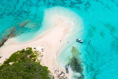 Aerial view of tourists, jet boat, idyllic empty sandy beach, remote island, azure turquoise blue lagoon, New Caledonia, Oceania. stock images