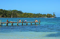 Tourists on a dock with tropical coast Royalty Free Stock Photos