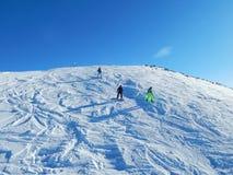 Tourists in Dombay - a downhill skiing resort in Karachayevo-Cherkesiya, Russia. At an altitude 3200 metres. Tourists in Dombay - a downhill skiing resort in Royalty Free Stock Photography