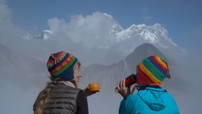 Girls in the Himalayas. Tourists drink tea against the background of clouds and snowy peaks. Nepal. Himalayas. Close-up. 4K stock footage