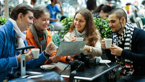 Tourists drinking coffee at cafe and reading city map Stock Images