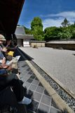 Tourists at the dry garden. Ryoan-ji zen temple. Kyoto. Japan. Ryōan-ji is a Zen temple located in northwest Kyoto; the Ryōan-ji garden is considered one of Royalty Free Stock Photography