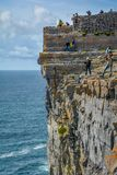 Tourists on Dun Aengus cliffs, Inishmore, Ireland. Inishmore, Aran Islands, Galway Bay, Ireland Stock Image