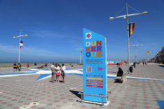 Tourists at Dunkirk beach in France. Dunkirk, France - May 31, 2017: Information board and tourists at the Malo les Bains beach resort of Dunkirk, France on May Stock Photo