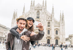 Tourists at Duomo cathedral,Milan. Happy tourists taking a self portrait with phone in front of Duomo cathedral,Milan - Couple travelling in Italy royalty free stock photo
