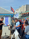 Tourists Eat Jellied Eel on Beach in Brighton. Stock Images