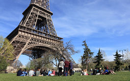 Tourists at the Eiffel Tower. Paris,France-April 1st, 2012: Groups of tourists lie in the grass in front of the famous Eiffel Tower in Paris. Eiffel Tower is one Stock Images
