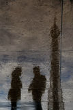 Tourists and the eiffel tower. Reflected on a wet sidewalk stock photo