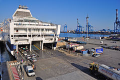 Tourists embark from the harbor of Genoa. GENOA - JUNE 24: tourists embark from the harbor of Genoa on the ferry to Sardinia for the summer holidays. June 24 royalty free stock image
