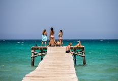 Tourists enjoy Alcudia bay sea view from a wooden jetty, Majorca Royalty Free Stock Images