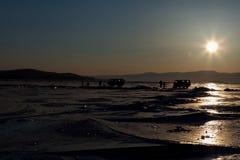 Tourists enjoy beautiful sunset moment at Olkhon island, Baikal lake, Russia. Tourists enjoy beautiful sunset moment at Olkhon island in the frozen Baikal lake royalty free stock image