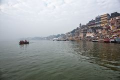 Tourists enjoy a boat ride on the holy Ganges river overlooking. The ancient architectural buildings and temples of Varanasi, India royalty free stock image