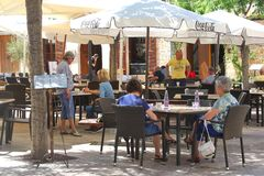 Tourists enjoy and chill at a cosy cafe terrace at the isle of Mallorca, Spain. People relax and enjoy at a cosy outdoor terrace in Alcudia at the isle of Stock Photos