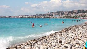 Tourists enjoy the good weather at the beach in Nice, France stock video