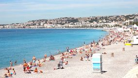 Tourists enjoy the good weather at the beach in Nice, France stock footage