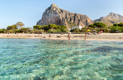 Tourists enjoy mediterranean sea in famous San Vito Lo Capo beach. Stock Photo