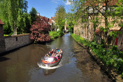 Tourists enjoy panoramic boat cruise along the canal, Bruges. Tourists enjoy panoramic boat tour on the canal, Bruges, Belgium Royalty Free Stock Image