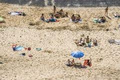 Tourists enjoy Papagayo beach on a sunny spring day Stock Photos