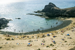 Tourists enjoy Papagayo beach on a sunny spring day Stock Images