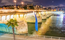 Tourists enjoy Seine river from Paris bridge at night.  Royalty Free Stock Photography