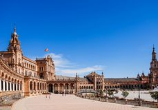 Tourists enjoy sightseeing around semi-circular building at the Plaza de España. stock image