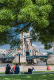 Tourists enjoy sun and shade by Tower Bridge in London. LONDON, UK - MAY 12, 2016: Tourists enjoy sun and shade by Tower Bridge on the Southbank of the Thames Stock Photo