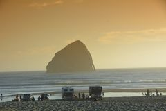 Tourists enjoy a sunset at Pacific City, Oregon Coast. Travelers with campers enjoy Haystack Rock off the coast of Oregon at Pacific City stock photography