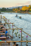 Tourists enjoy sunset in river cafe in Vang Vieng village, Laos. Vang Vieng, Laos - January 19, 2017: Tourists enjoy sunset in river cafe in Vang Vieng village Stock Photos