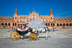 Tourists enjoy a trip on horsedrawn cart on Plaza de Espana, Seville, Spain. stock photos