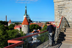 Tourists enjoy the view of Oleviste church and old town of Tallinn from the observation platform on Toompea hill Royalty Free Stock Photos