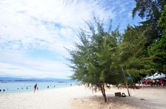 Tourists enjoy white sand beach of Sapi island in Sabah Stock Images