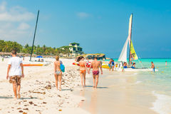 Tourists enjoying the beach at Varadero in Cuba. VARADERO,CUBA - APRIL 28,2014 : Tourists walking along the shore and boarding a sailing boat on a beautiful Stock Image
