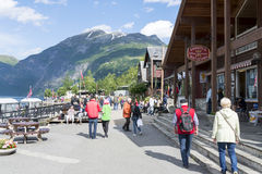 Tourists enjoying the beautiful weather walking through the streets of Geiranger on June 29, 2016 in Geiranger, Norway. Geiranger is UNESCO heritage site Stock Photo