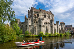Tourists enjoying a boat ride on the river near Gravensteen castle Royalty Free Stock Images
