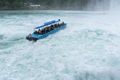Tourists enjoying boat trip in Rheinfall waterfall in Switzerland