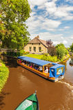 Tourists enjoying a canal cruise with a wooden boat in the famou Royalty Free Stock Photos