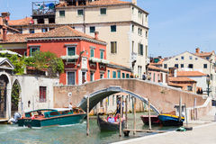 Tourists enjoying the gondolas in a canal in Venice Stock Photography
