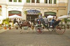 Tourists enjoying horse carriage ride in Old Havana, Cuba Stock Photos