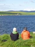Tourists enjoying scenery. Two tourists sitting together looking over the landscape of Orkney Island, Scotland stock photography