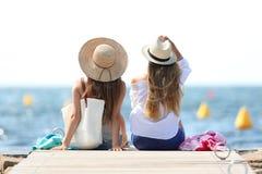 Tourists enjoying summer holidays on the beach. Back view of two tourists enjoying summer holidays on the beach stock photos