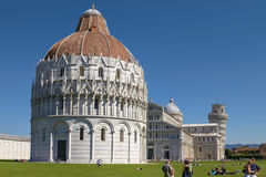 Tourists Enjoying Sunny Day in Front Of Baptistery at Leaning Tower of Pisa in Tuscany Italy Royalty Free Stock Image