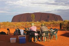 Couple enjoys the sunset at Ayers Rock and has a picknick, Australia