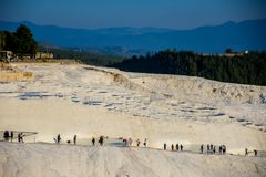 Tourists enjoying in the termal water pools in Pamukkale. Tourists swimming and walking in the thermal water pools in Pamukkale Stock Image