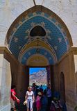Tourists entering arch gate with colorful paintings at Panormitis Monastery. stock photography