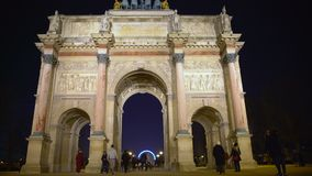 Tourists entering Tuileries Garden through triumphal arch in Place du Carrousel. Stock footage stock video