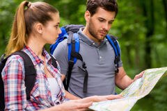 Tourists examining map. Thoughtful young couple with backpacks examining map while standing in nature Stock Image