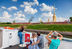 Tourists at the excursion boats look on Peter and Paul Fortress Stock Images