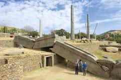 Tourists explore famous collapsed obelisks of Axum, Ethiopia. AXUM, ETHIOPIA - JANUARY 24, 2010: Unidentified tourists with a guide explore famous ruins of Royalty Free Stock Images