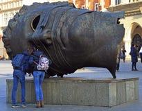 Tourists are exploring Head sculpture Eros Bendato by polish artist Igor Mitoraj on Market Square in Krakow, Poland Royalty Free Stock Photo